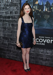 Bonnie Wright accented her fitted navy dress with a gold and tortoiseshell Minaudière Bijou Clutch.
