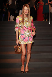 Anna dello Russo completed her ensemble with a cute gold straw tote.