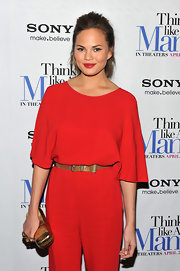 Chrissy Teigen's gold clutch provided a striking color contrast to her red jumpsuit at the 'Think Like a Man' screening.