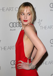 Dakota Johnson was sexy-glam at the Heaven Gala wearing diamond and pearl cuffs with a red halter dress.