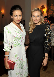 Camilla Belle paired a pink Miu Miu satin clutch with a floral frock for an ultra-feminie look during the Muta event.