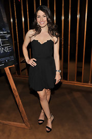 Sarah Shahi paired a black sweetheart dress with strappy black and gold sandals.
