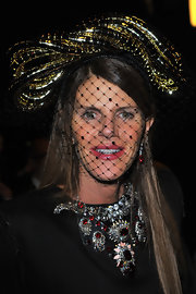 Anna dello Russo attended the Lanvin fashion show wearing one of her avant-garde headpieces--a veiled fascinator that looked like a gold snake sitting atop her head.