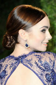 Lily Collins complemented her updo with a stunning pair of dangling gemstone earrings.