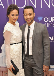Chrissy Teigen kept it classic with a black frame clutch teamed with a white lace dress at the Inaugural Youth Ball.