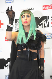Lady Gaga punched up her outfit with a black feather necklace by Roggykei for the MTV Video Music Aid Japan press conference.