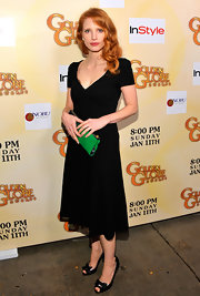 Jessica Chastain accessorized with a bright green suede clutch for a spot of color to her black dress.