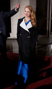 Jessica Chastain kept her BAFTA gown safe from the rain with a black-and-white Roland Mouret trenchcoat.