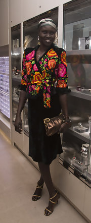 Alek Wek complemented her outfit with a super-sophisticated metallic gold snakeskin clutch.