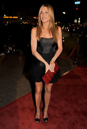 Jennifer Aniston arrived for the premiere of 'Marley & Me' carrying a red snakeskin clutch by Ferragamo.