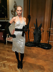 Poppy Delevingne contrasted her silver dress with black accessories, including a dramatic pair of full-sleeve gloves.