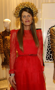 Anna dello Russo contrasted her modest dress with a head-turning veiled gold fascinator by Alan Journo when she attended the Valentino flagship store opening.