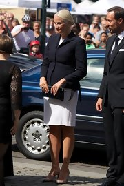 Princess Mette-Marit finished off her ensemble with a croc-embossed patent clutch.