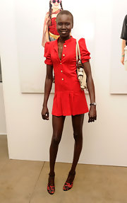 Alek Wek teamed her mini dress with a pair of cute red and black ankle-strap sandals.