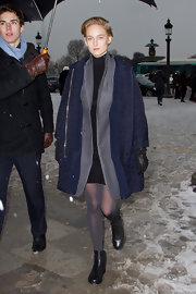 Leelee Sobieski battled the Paris chill with a navy tweed coat as she arrived for the Dior fashion show.