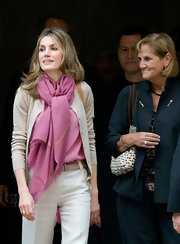 Princess Letizia added color and flair to her outfit with a voluminous pink scarf when she visited Montserrat Abbey.