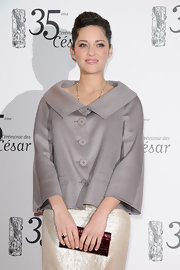 Marion Cotillard paired a red Dior patent clutch with a chic gray swing jacket for the Cesar Film Awards.
