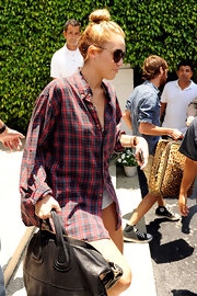 Miley Cyrus headed out of her Miami hotel wearing an oversized plaid button-down shirt.