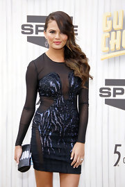 Chrissy Teigen styled her sexy dress with a sophisticated black and silver hard-case clutch when she attended the Guys Choice event.