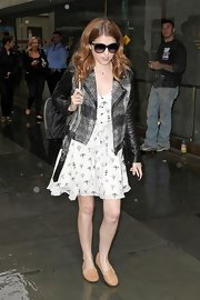 Anna Kendrick was spotted outside Rockefeller Plaza wearing nude smoking slippers, a moto jacket, and a print dress.