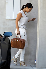 Kim Kardashian stepped out in Hollywood rocking an all-cream outfit, consisting of Balmain skinny jeans, a silk top, and Tom Ford strappy heels.