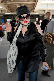 Cyndi Lauper was spotted at the airport in Nice, France wearing a satin button-down shirt with shoulder cutouts and a pair of jeans.