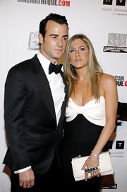 Jennifer Aniston arrived for the American Cinematheque Award carrying a white Valentino clutch with a studded hand strap.