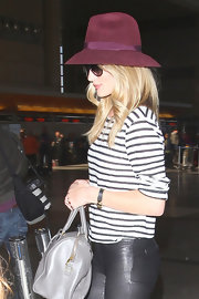 Rosie Huntington-Whiteley kept her face hidden under a purple suede hat as she made her way through LAX.