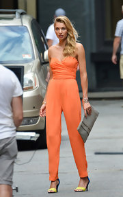Jessica Hart complemented her jumpsuit with a stylish zigzag-print clutch.