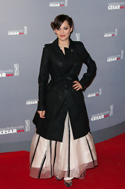 Marion Cotillard hid her gown under a black trenchcoat as she arrived for the Cesar Film Awards.