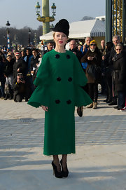 Ulyana Sergeenko totally stole the limelight in a green coat with huge black buttons and elaborate trumpet sleeves during the Chloe fashion show.