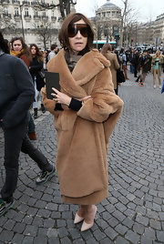 Carine Roitfeld cozied up in luxurious style with a Max Mara teddy bear coat during the Miu Miu fashion show.