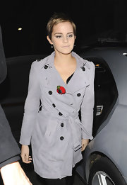 For a splash of color to her gray coat, Emma Watson accessorized with a Swarovski crystal poppy brooch.