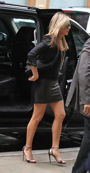 Edgy-glam metal-back sandals by Giuseppe Zanotti finished off Jennifer Aniston's look.