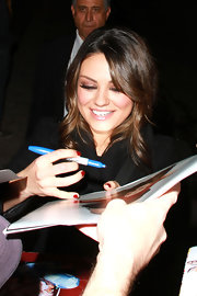 Mila Kunis showed off a perfect red mani while signing autographs.