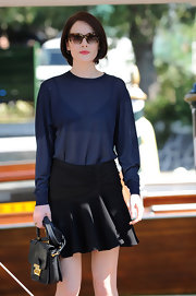 Michelle Dockery shaded her eyes with a pair of rectangular tortoiseshell sunnies while headed to the Miu Miu Women's Tales Talks photocall.