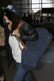 Kristen Stewart caught a flight out of LAX carrying a big navy duffel bag by Fjallraven.