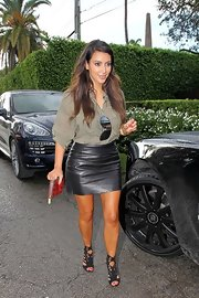 Kim Kardashian teamed a tan Isabel Marant button-down with a black leather mini for a day out in Miami.