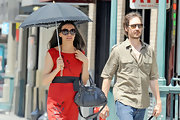 Famke Janssen strolled around Greenwich Village wearing a chic red dress and a gray hobo bag on one arm.