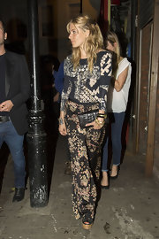 Sienna Miller styled her outfit with an elegant black crocodile clutch.