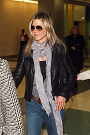 Jennifer Aniston contrasted her tough-looking jacket with a sweet lavender polka-dot scarf by Faliero Sarti for a flight.