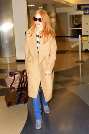 Jessica Chastain bundled up in a beige Michael Kors double-breasted coat for a flight.