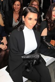 Kim Kardashian sat front row at the Stephane Rolland show wearing black leather gloves and a cape.