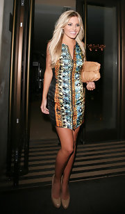 Mollie King styled her dress with a beige snakeskin clutch.