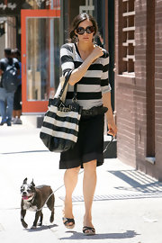 Famke Janssen matched her top with a striped tote as she walked her dog.
