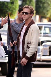 A gun-toting Ryan Gosling rehearsed a scene for 'Gangster Squad' while wearing a pair of brown wayfarers.