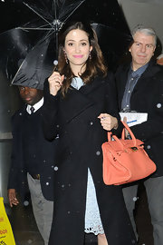 Emmy Rossum added sweet color to her outfit with this peach leather tote during her visit to 'Live! with Kelly and Michael.'