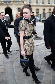 Lily Collins made her way to the Louis Vuitton fashion show carrying a stylish blue leather purse from the label.