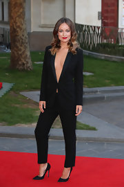 Olivia Wilde oozed sex appeal in a cleavage-baring black pantsuit during the London premiere of 'Rush.'