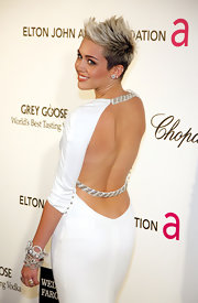 Miley Cyrus teamed Lorraine Schwartz diamond chain bracelets with a backless gown for a sexy-glam look during the Elton John AIDS Foundation party.